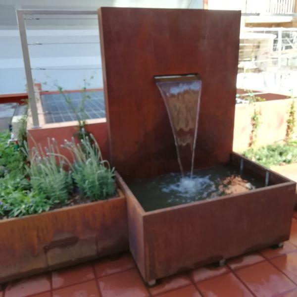 fuentes y jardineras de acero corten combinadas sobre terraza